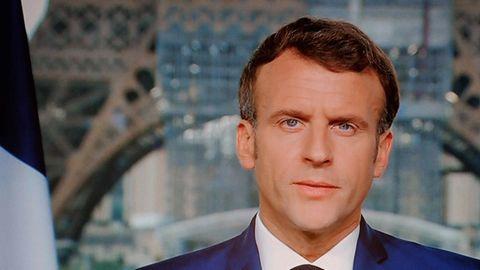 Ein weißer Mann mit braunem Seitenscheitel sitzt im blauen Anzug und schwarzer Krawatte in einem TV-Studio