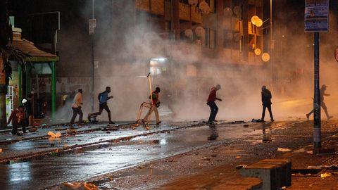 Südafrika, Johannesburg: Demonstranten laufen weg nachdem die Polizei Tränengaskanistern eingesetzt hat