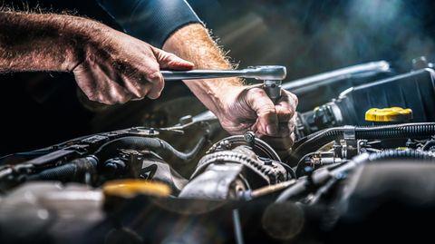 Ein Mechaniker schraubt an einem Automotor