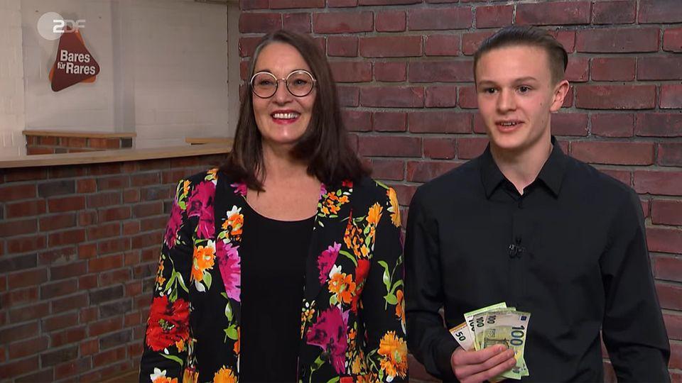Petra und Moritz Greiner stehen im Studio von Bares für Rares mit einem Bündel Geld in der Hand