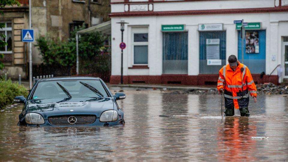 Mann watet über überflutete Straße