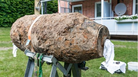 Eine mit Erde und Rost überzogene Bombe liegt auf einem Gestell vor einem Mehrfamilienhaus