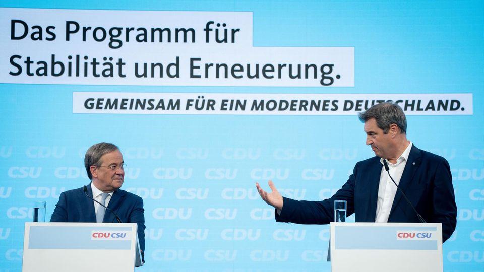 Auf einer Bühne mit hellblauem Hintergrund stehen zwei Rednerpulter, an denen zwei weiße Männer in Anzügen stehen