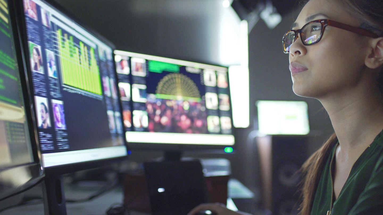 Zwei Monitore anschließen: Eine Frau blickt auf mehrere Monitore.