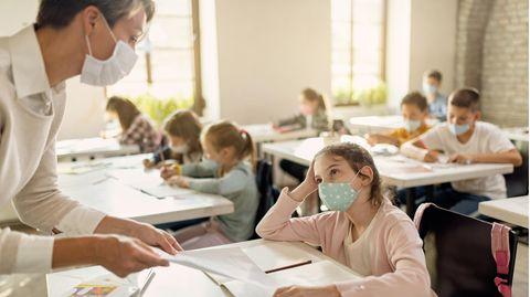 Schülerin mit Gesichtsmaske im Gespräch mit einem Lehrer
