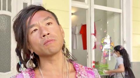 Ein asiatisch aussehender Mann mit längeren Haaren und Feder-Ohrring legt den Kopf schräg und steht er vor einem gelben Altbau