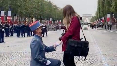 Mitten auf den Champs-èlysées kniet ein Soldat in Gardeuniform vor seiner blonden Freundin, die steht