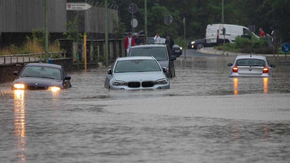 Nach Starkregen bahnen sich Autos ihren Weg über überflutete Straßen