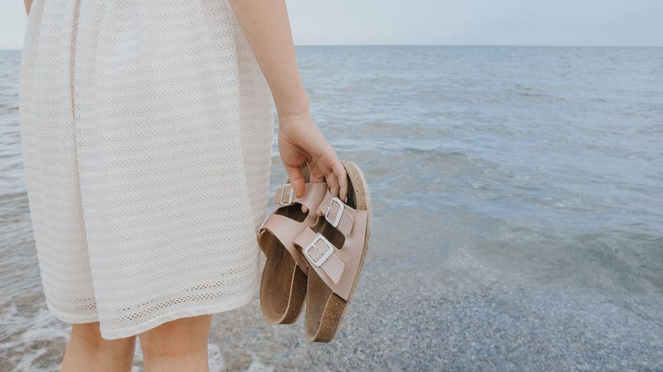 Frau im Kleid hat Sandalen in der Hand