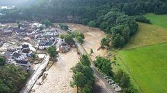 Auf einer Luftaufnahme ist ein Ort zu sehen, um den sich ein Hochwasser führender brauner Fluss windet