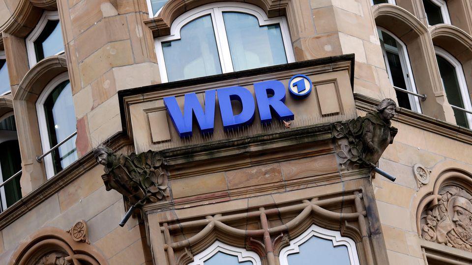 An einer Hausfassade hängt ein blaues Schild mit der Aufschrift WDR