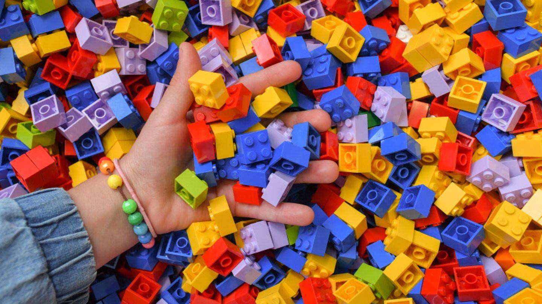 Ein Mädchen greift in eine Kiste voller Lego-Steine