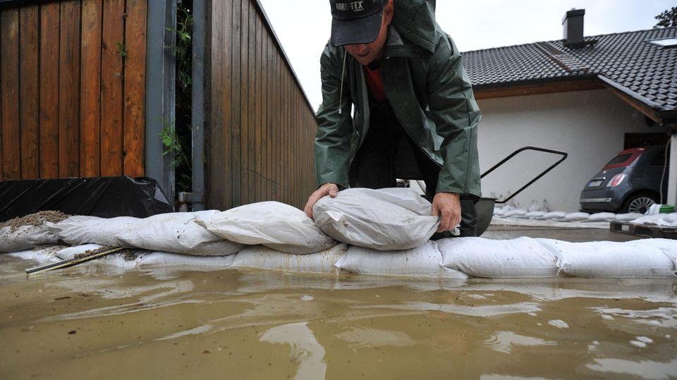 Ein Mann schützt sein Haus mit Sandsäcken. Dieses Foto stammt von 2010, damals ließ Dauerregen amStarnberger See zahlreiche Häuser volllaufen