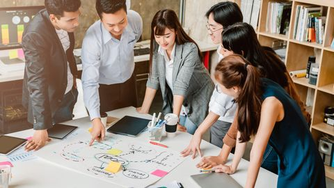 Ein Team steht um einen Tisch herum und schaut auf einen Plan.
