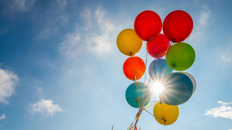 Bunte Luftballons vor blauem Himmel