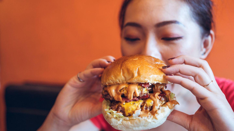 Eine Frau beißt in einen Burger