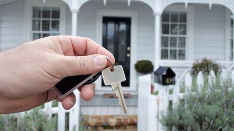 Eine Hand hält eine Schlüssel vor einem Haus in die Kamera