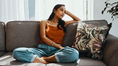 Frau sitzt auf dem Sofa und guckt verträumt zur Seite.