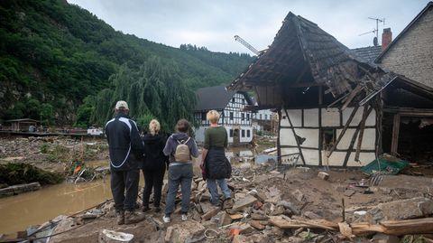 Zwei Erwachsenen und drei Kinder stehen am Ufer eines Flusslaufes inmitten von Schlamm und Trümmern.