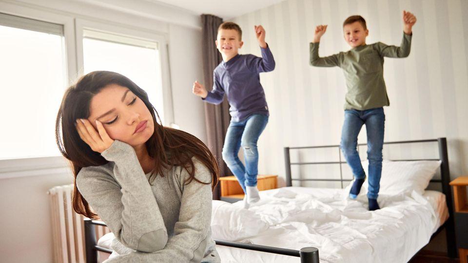 Mutter sitzt müde vor dem Bett ihrer Kinder, die im Hintergrund darauf herumspringen.