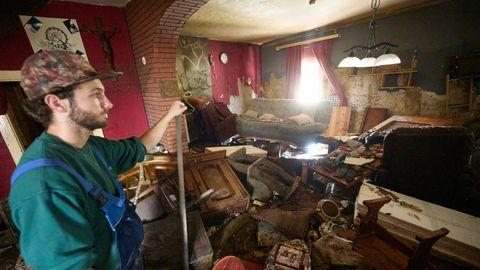 Ein junger Mann mit Vollbart und Cap steht auf eine Schuafel gestützt in einem von Wasser verwüsteten Wohnzimmer