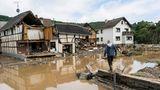 Ein Mann in Gummistiefeln und Arbeitshose geht auf einem Mäuerchen auf ein vom Wasser zerstörtes Fachwerkhaus zu
