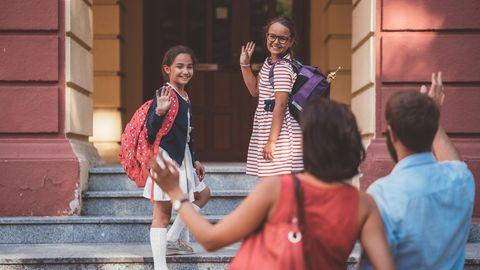 Kinder verabschieden sich winkend von ihren Eltern und gehen in die Schule