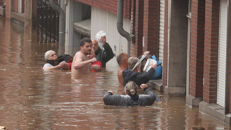 Sechs Menschen stehen teils bis unter die Achseln im Hoochwasser und versuchen, ihre Habseligkeiten trocken zu halten