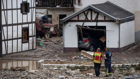 Zwei Rettungskräfte stehen im Dorf Schuld im Schutt vor einem zertrümmerten Haus