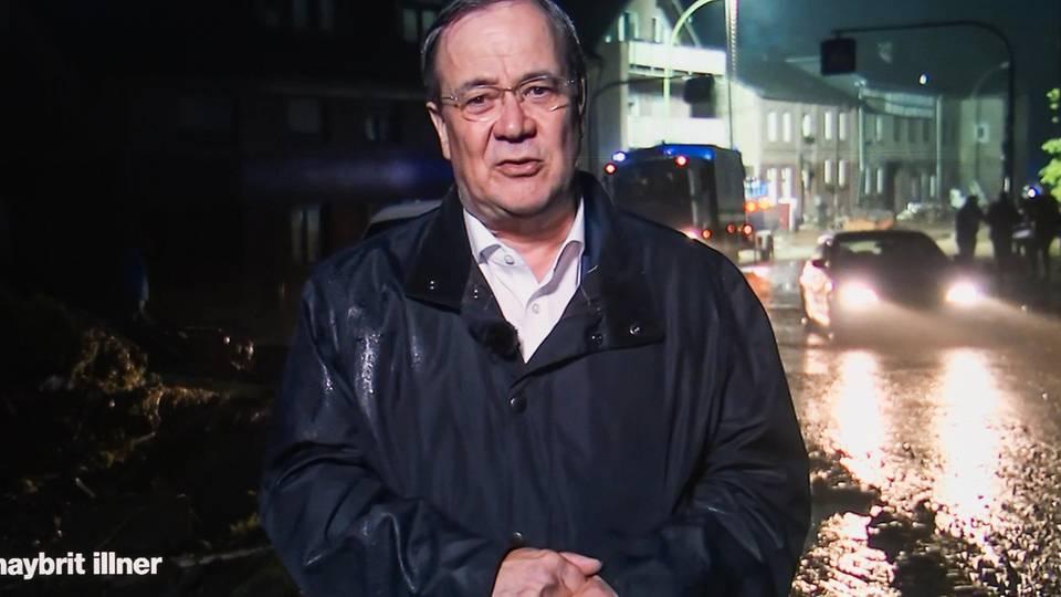 Armin Laschet in der Zuschalte bei Illner, er steht im Regenmantel vor einer verregneten Straße
