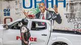 EIn Polizist und ein weißes Auto vor dem Bildnis des ermordeten haitianischen Präsidenten Jovenel Moïse