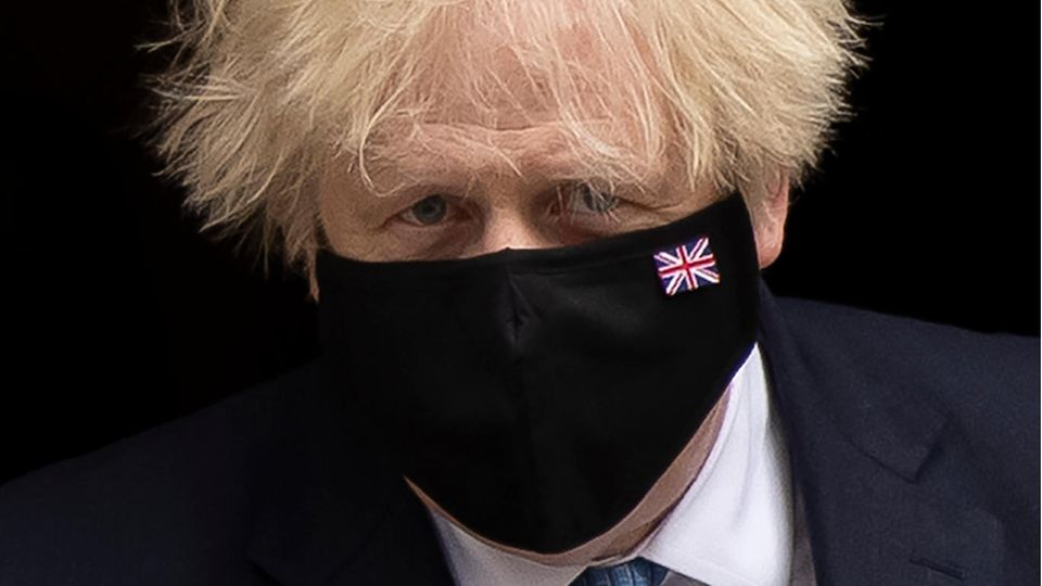 Boris Johnson trägt eine schwarze Maske mit der britischen Flagge
