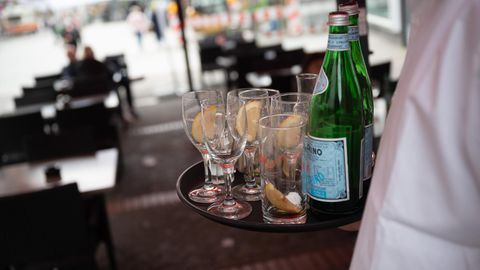 Eine Servicekraft räumt leere Gläser und Flaschen ab