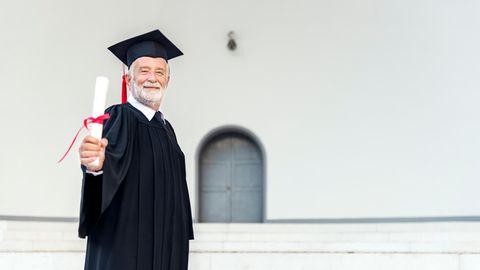Ein älterer Herr mit seinem Uni-Diplom