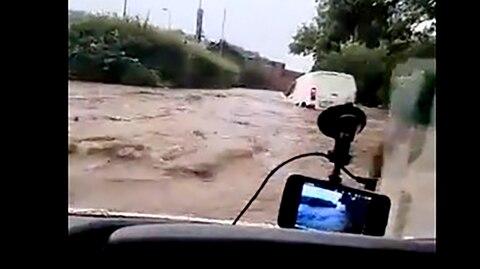 Ein Autofahrer fährt durch Hochwasser