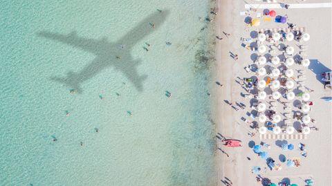 Strandgäste blicken auf eine Flugzeug-Silhouette