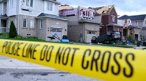 Hinter einem gelben Absperrband stehen beschädigte Häuser. Vor einem liegt ein SUV auf dem Dach in der Einfahrt