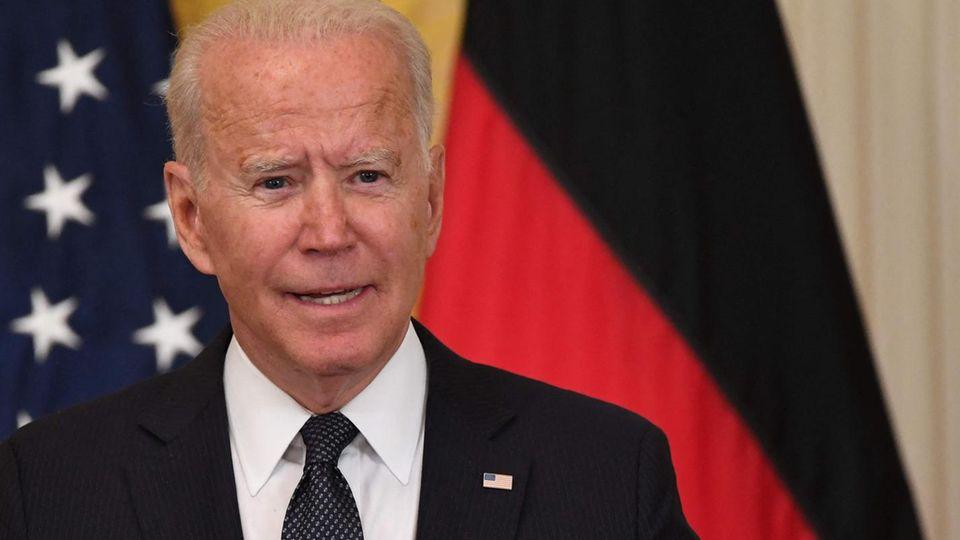 Ein weißhaariger ältere weißer Mann steht in Anzug und Krawatte an einem Rednerpult vor einer US- und einer deutschen Flagge