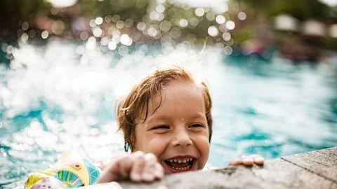 Ein Junge hängt im Freibad am Beckenrand
