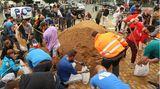 In Erftstadt befüllen Dutzende von Helfern diverse Sandsäcke, die benötigt werden, um Dämme zu sichern, die vom Hochwasser aufgeweicht sind.