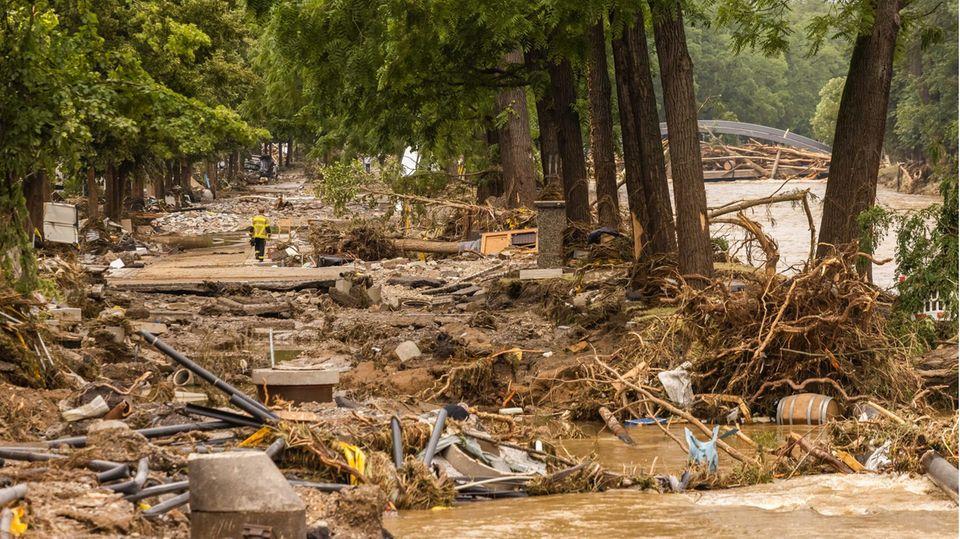 Trümmerfeld durch Hochwasser:Ein Feuerwehrmann geht durch die Reste einer Straßein Bad Neuenahr in Rheinland-Pfalz.