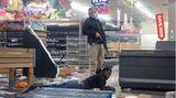 Ein Polizist hält inJohannesburg einen Verdächtigen fest, der ein Geschäft geplündert hat.