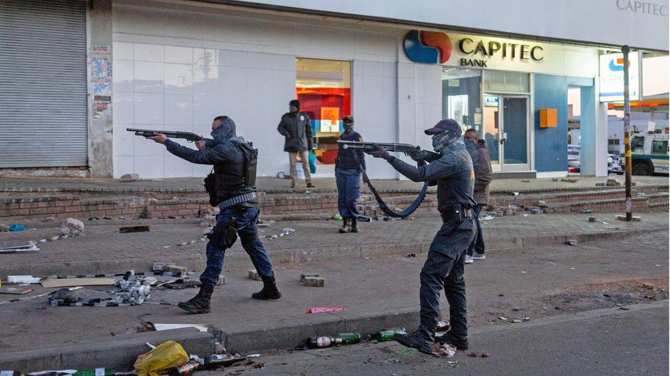Hier stehen Soldaten in Johannesburg mit Schrotflinten imAnschlag auf der Straße, um mit Plünderungen fertig zu werden.
