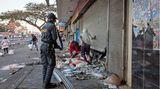Im Angesicht der Ordnungskräfte: Plünderer kommen aus einem Geschäft