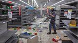 Supermarkt mit leeren Regalen:Ein Polizist geht durch ein geplündertes Geschäft inJohannesburg.
