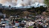 Spuren der Gewalt in Durban: Rauch steigt aus einer Fabrik im Hintergrund auf, während leere Kisten von geplünderten Waren auf einer Fahrbahn liegen.