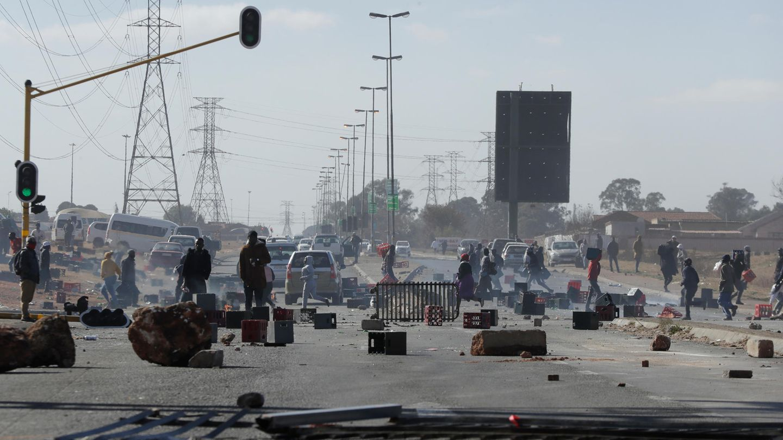Während der anhaltenden Unruhen und Plünderungen in Südafrika: Demonstranten stehen hinter Barrikaden auf einer Straße in Soweto.