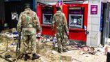 Nichts als Chaos: : Zwei bewaffnete Soldaten stehen nach den Ausschreitungen vor den Geldautomaten einer Bank.