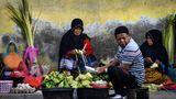 Banda Aceh, Indonesien: Auf einem Markt verkauft diese Frau Ketupat, einen traditionellen Reiskuchen. Dafür wird Reis in kleine Päckchen aus gewebten Palmblättern gefüllt und anschließend gekocht.
