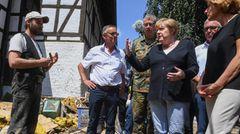 Merkel im Gespräch mit einem Einwohner von Schuld